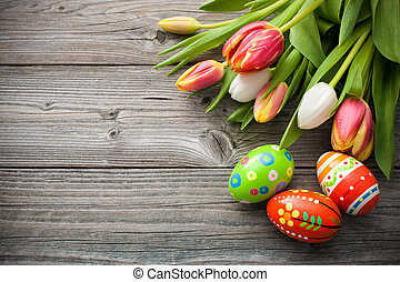 Easter eggs with tulips on weathered wooden background