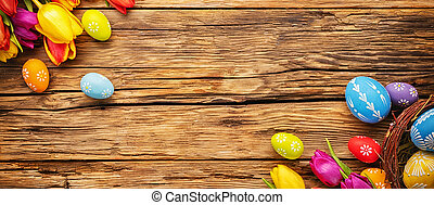 Easter eggs with tulips on wooden board