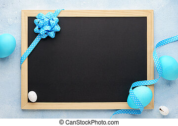 Easter frame with blue eggs and empty chalkboard.