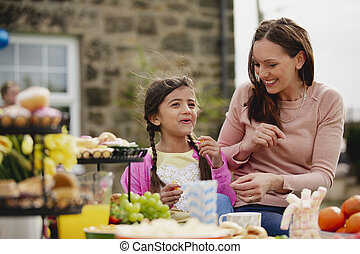 Easter Garden Party - Young girl and her mother sitting...