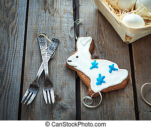 Easter gingerbread with a festive glaze in the shape of a hare and a small basket with chicken eggs lie on a wooden rustic table