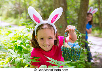Easter girl with eggs basket and funny bunny face expression...