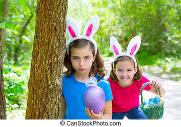Easter girls playing on forest with bunny teeth gesture