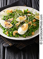 Easter green peas salad, micro green, nuts and boiled eggs close-up on a plate. vertical