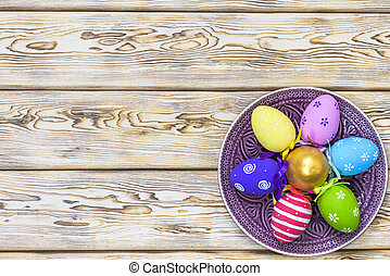 easter, holidays, tradition, advertisement and object concept - close up of colored easter eggs on plate
