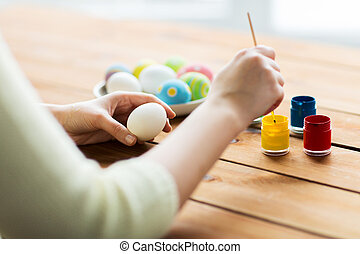 close up of woman coloring easter eggs
