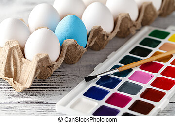 easter, holidays, tradition concept - close up of coloring easter eggs with colors and brush