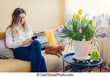 Easter home decor. Woman and cat relax on couch. Spring blooming flowers in pot decorated with eggs and bunny.