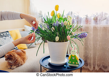 Easter home decor. Woman hangs eggs on spring blooming flowers in pot. Yellow hyacinths, tulips, muscari.
