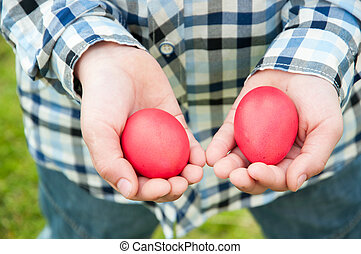 Easter hunt - two red eggs in hands