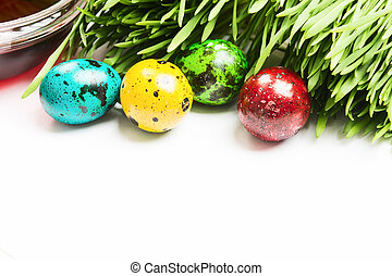Easter hunt with colorful small quail eggs and green grass on white background with copy space. Selective focus
