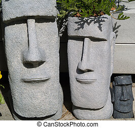 Two Easter Island garden planters next to some other clay planter pots with plants in all.