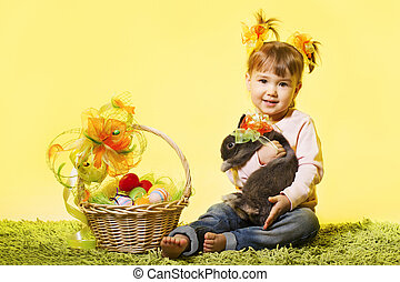 easter little girl, kid holding bunny rabbit basket eggs over yellow background