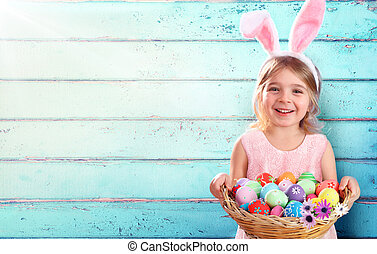 Easter - Little Girl With Basket Eggs And Bunny Ears And Blue Wooden Background