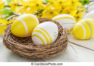 Easter nest with yellow easter eggs on a white wooden background