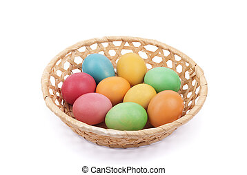Easter painted eggs in a basket, isolated on white.