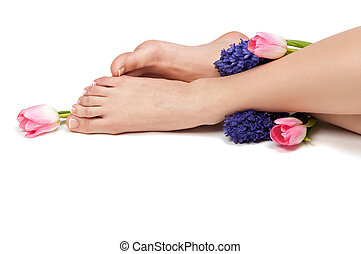 Pedicured feet and aromatic flowers in a spa