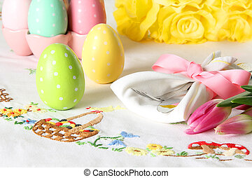 Easter place setting on an elegant linen table cloth. This traditional holiday brunch place setting includes painted eggs, an embroidered Easter basket, silver cutlery wrapped in a napkin and springtime pink tulips.