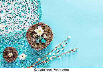 Easter quail eggs in bird nest on blue background, flat lay, copyspace. Easter holiday decorations , Easter concept background - Image