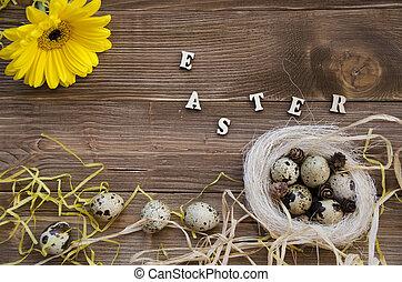 Easter quail eggs in nest on wooden background