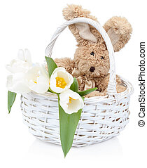 Easter rabbit with white tulips in a basket