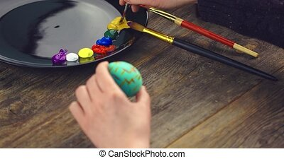 Easter religious christian holiday. Close up video of female hands painting on egg with paintbrush. High quality 4k footage