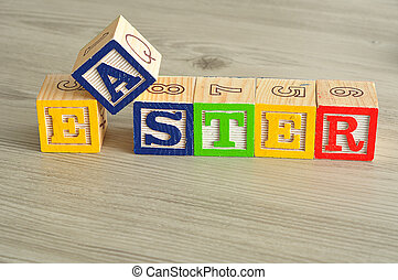 Easter spelled with colorful alphabet blocks isolated against a wooden background