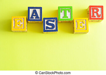 Easter spelled with colorful alphabet blocks isolated against a yellow background