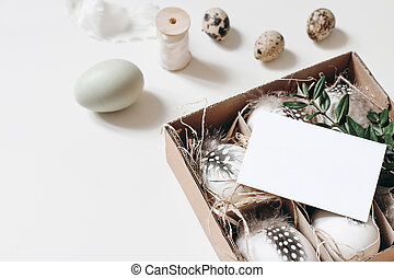 Easter, spring still life. Greeting card, invitation mockup on paper box with quail and hen eggs, feather and green branch isolated on white table. Feminine styled photo, top view. Blurred background.