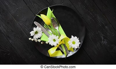 Easter spring table dishware composition with yellow tulip...