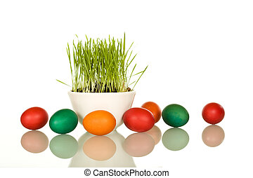 Easter symbols - fresh green grass and colorful eggs