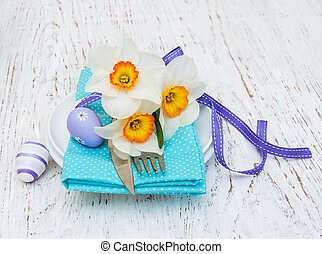easter table setting with daffodil flowers on a old wooden...