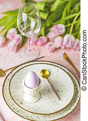 Easter table setting with cutlery, pink tulip flowers and easter eggs on pink table.