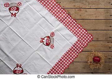 Easter tablecloth on a wooden surface with a nest