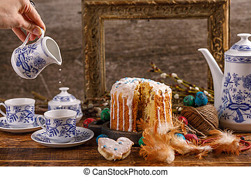 Easter tea, milk is poured into a cup of tea. Fresh homemade cake in sugar icing for the holiday. Easter decorations on the table.