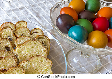 Easter traditional bread and colorful Easter eggs in a plate on the table