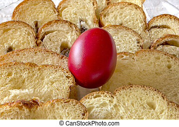 Easter traditional bread and red chicken egg in a plate on the table