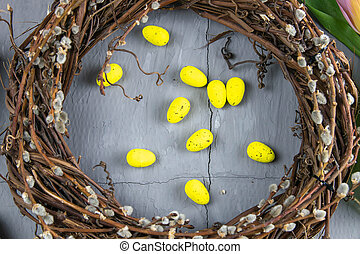 Easter willow wreath and blue Easter eggs on blue background. Top view, copy space