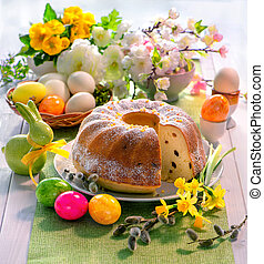 Easter yeast cake with icing on holiday table decorated with...