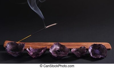Eastern aromatherapy. Dry flowers and steaming incense on a dark background 4k