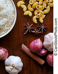 eastern food spice herb rice garlic  red onion cinnamon on wood table background