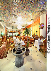 eastern interior of beautiful restaurant, potted palms and fountain