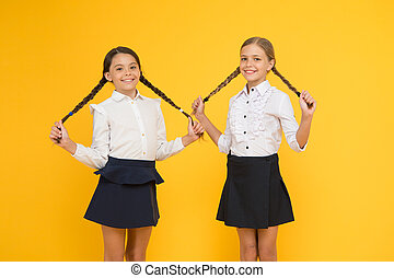 Easy back to school hairstyle. Cute small girls with long hairstyle on yellow background. Adorable little children holding braided hairstyle. Getting your hairstyle to last all day