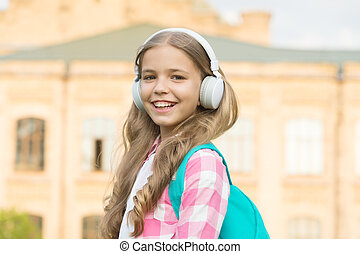 Easy listening and dreaming. Happy girl enjoy listening to music. Small child practise listening skills. Listening course. Distance learning. Remote training. School and education. Modern life