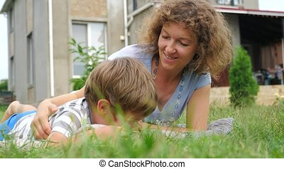 Easy parenting concept. Happy mother and child lying on the grass.