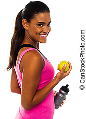 Athletic woman holding sipper bottle and fresh green apple