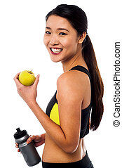 Fitness woman holding sipper bottle and fresh green apple