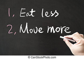 Eat less and move more words written on the blackboard using...