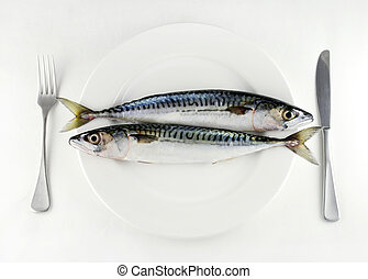 eat more fish - two mackerel on a white plate with knife and...