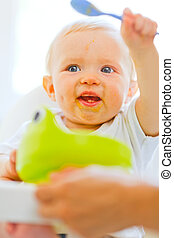 Eat smeared adorable baby girl in baby chair playing with...